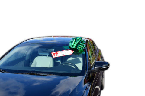 green pull bow on car with gift tag