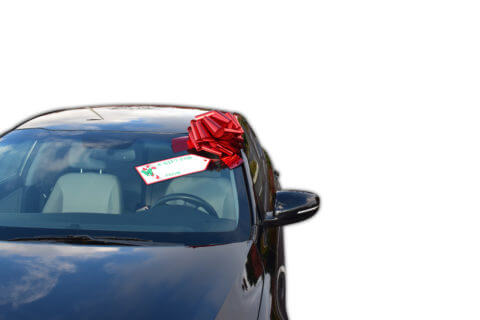 big red car bow on black car with gift tag