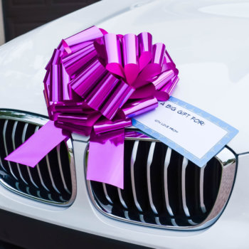 big pink car bow on a white car with a gift tag