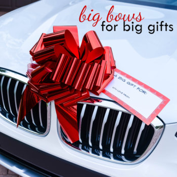 big red car bow on a white car with a personalized gift tag