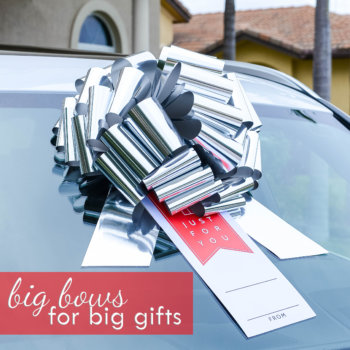 giant silver car bow with a personalized gift tag on a car suction cup